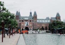 "A park with a sign that says ""I amsterdam"" in front of a gabled building."