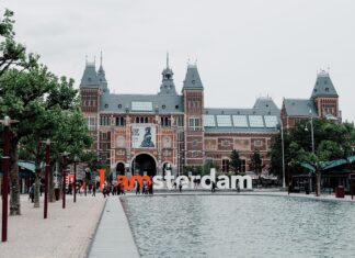 """A park with a sign that says """"I amsterdam"""" in front of a gabled building."""