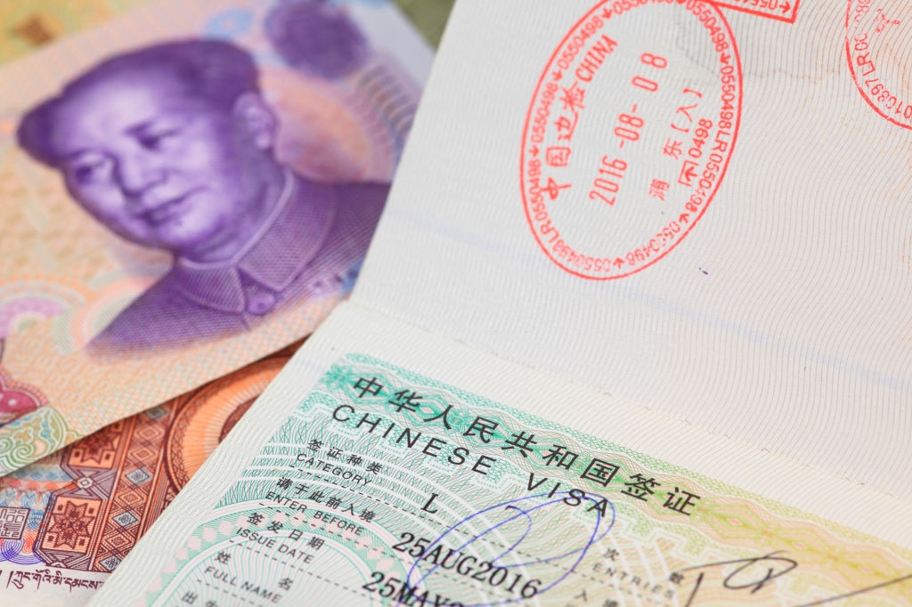 Chinese Visa with Chinese yuan bank note as a background