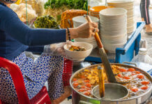 A street food vendor cooking crab paste and snail noodle soup at the street side of Hanoi