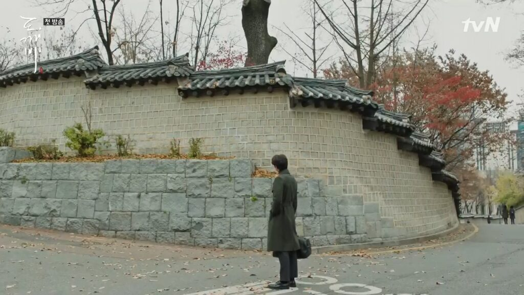A man staring at a stone wall.