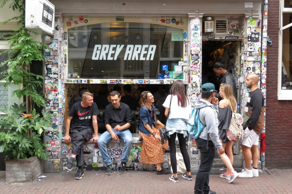 "People in front of a shop with a signage that says ""Grey Area"""