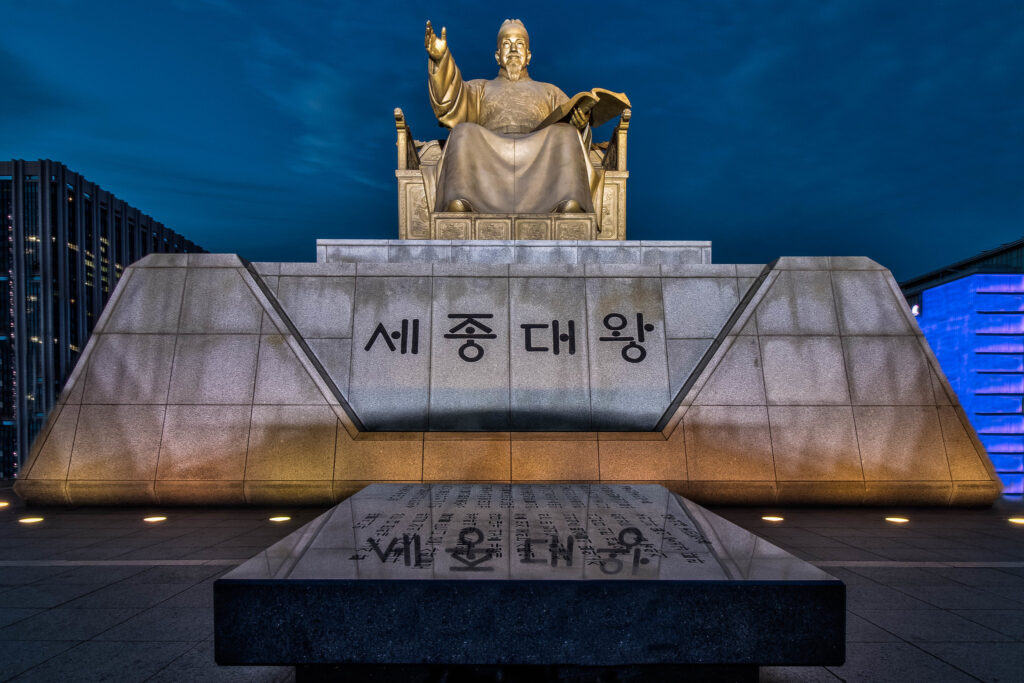 The statue of King Sejong in Gwanghwamun Square at night.