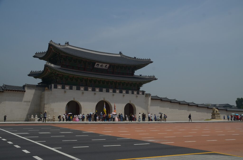 People outside the gate of a Korean traditional palace.