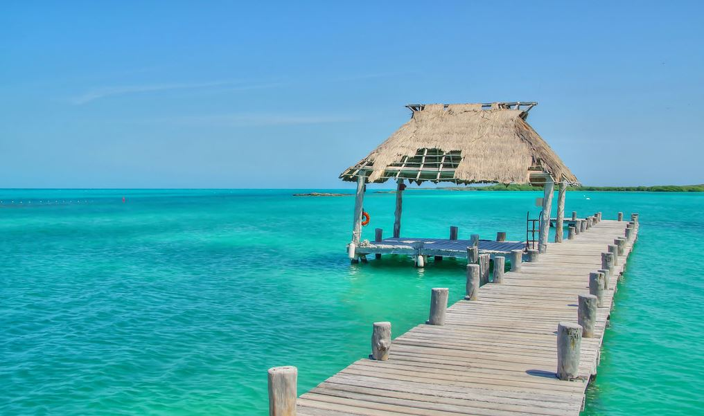 A wooden walkway leading to a hut on the middle of the sea.