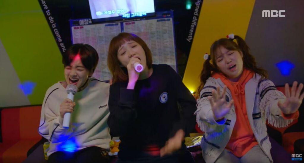 Three girls singing in a karaoke.