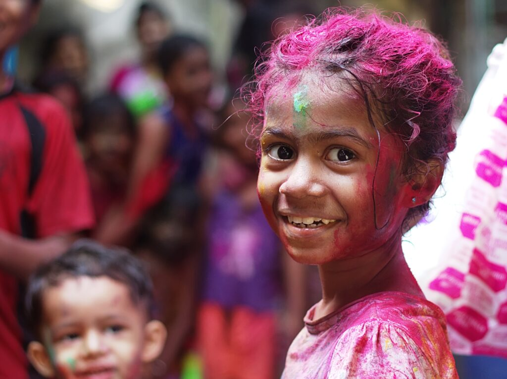 A smiling little girl covered with colored powder.