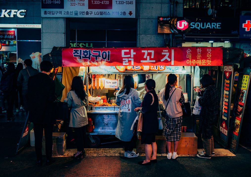 People in front of a food cart buying Korean street foods.