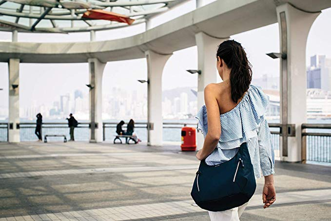 A women traveling with Pacsafe blue color anti-theft convertible length crossbody walking on the street