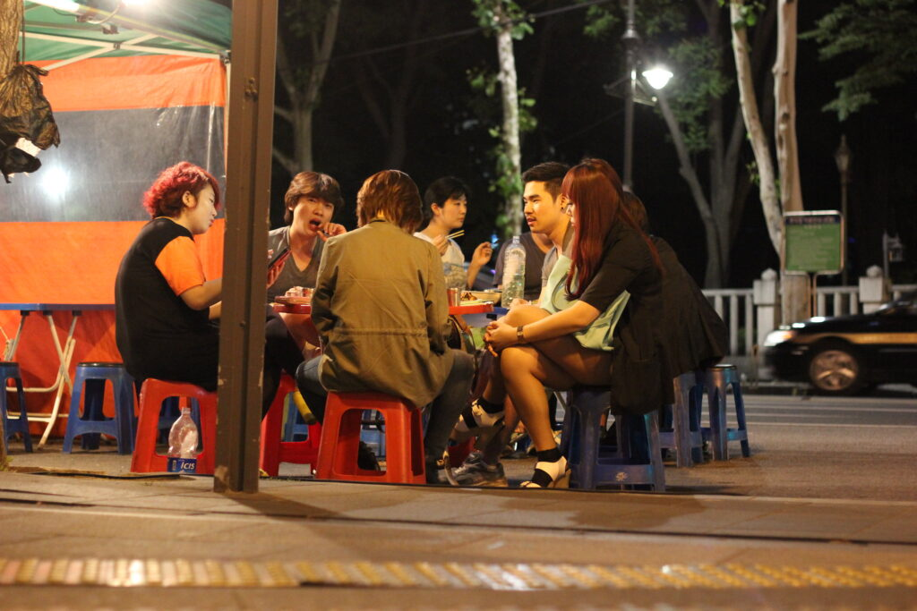 A group of people sitting outside a Pojangmacha, tent bars in Korea.