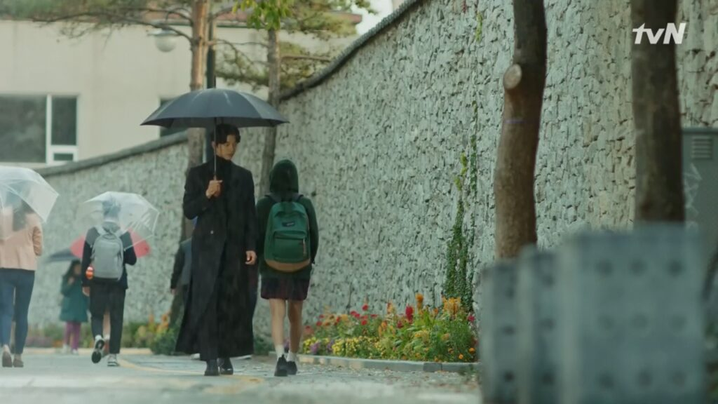 A girl in a hoodie jacket walks past a man carrying a black umbrella.