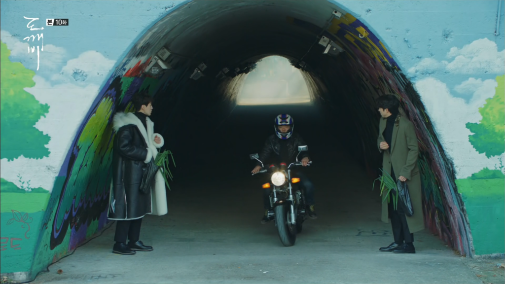 2 men watching a passing motorcycle between them in a tunnel.