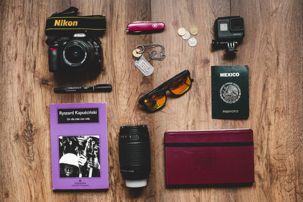 Flat lay photograph of travel essentials like passport, camera, planner, etc..