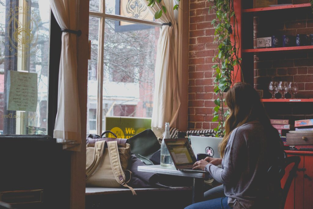 A girl using a laptop near the window.