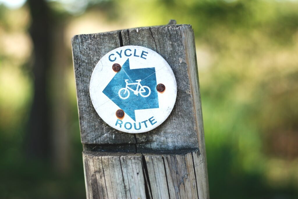 A sign in a wooden post that says cycle route.