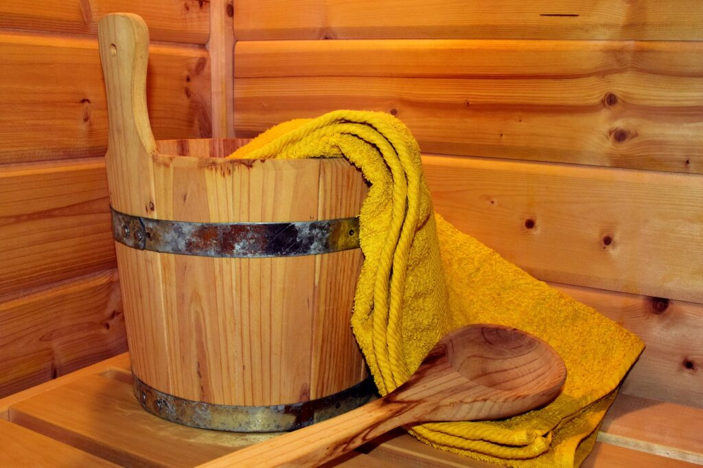 A wooden pail and water dipper in a sauna.