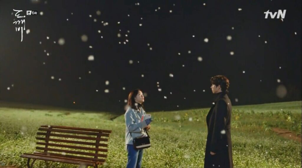 A man and a woman standing next to a bench in a green field while snowing.
